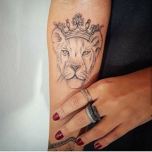 Women's lion with crown tattoo