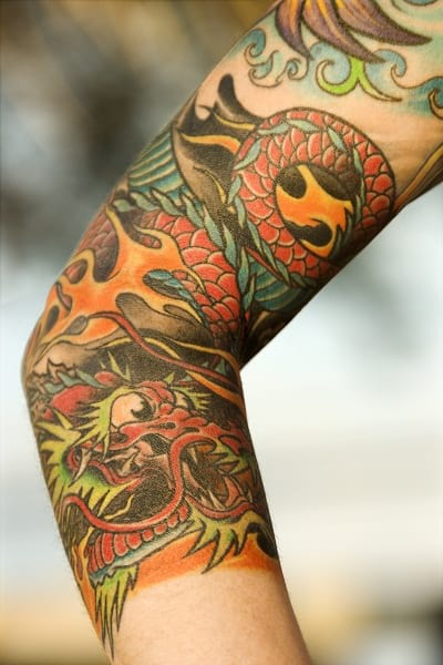 Unique hand sleeve tattoo of Japanese Dragon